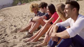 Group of multiracial people sitting on a beach