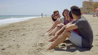 Group of trendy young friends sitting on a beach