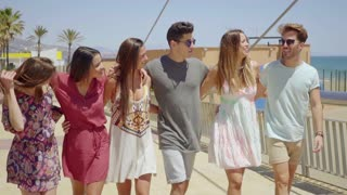 Group of trendy young friends walking arm in arm
