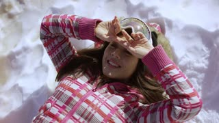 Half body portrait of happy young woman lying on snow with ski goggles and arms stetched out on ground