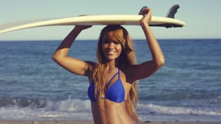 Half Body Shot of a Pretty Smiling African Woman in Bikini Holding Surfing Board Overhead at the Beach.