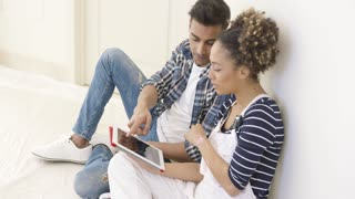 Handsome black couple sits and uses tablet while seated on tarpaulin and against a white wall
