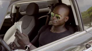Handsome black man seated in car with phone
