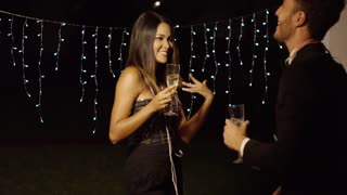 Handsome couple flirts with champagne in hand while standing near pillar icicle string lights