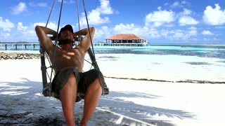 Handsome Man is Sleeping on Beach Swing