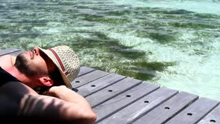 Handsome man resting near water at Maldives