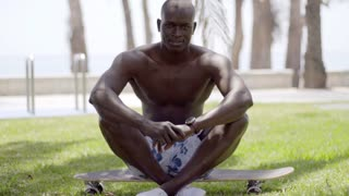 Handsome shirtless black man seated on skateboard