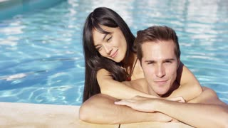 Handsome smiling couple cuddles in swimming pool on lovely summer afternoon
