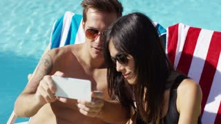 Handsome young man in sunglasses taking picture of himself with smiling wife at outdoor swimming pool
