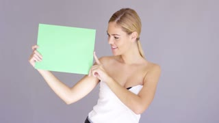 Happy attractive young blond woman in a strapless top holding up a blank green sign to the side and looking at it with a smile