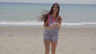 Happy beautiful woman walking near beach