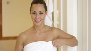 Happy beautiful young adult woman holding white towel around herself as she exits the bathroom