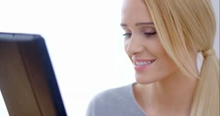 Happy Blond Girl Using her Tablet Computer