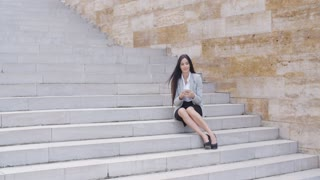 Happy executive with phone and seated on stairs