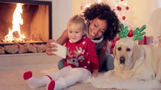 Happy family selfie portrait at Christmas with a happy smiling young woman photographing herself with a small girl and dog in reindeer antlers on the living room floor in front of a blazing fire.