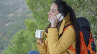Happy female hiker on phone