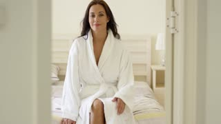 Happy friendly young woman in a white bath robe sitting on the end of her bed in the morning smiling at the camera