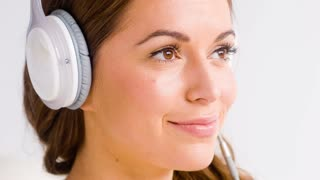Happy Girl Listen Music in White Headphones and Smiling