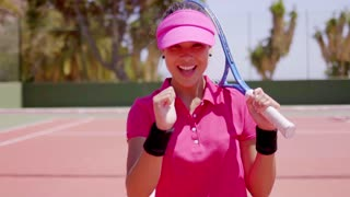 Happy gorgeous young female tennis player in a trendy pink outfit giving a thumbs up of success with a beaming smile