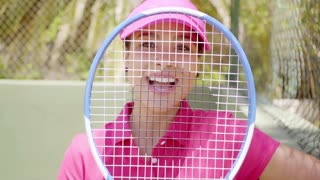 Happy gorgeous young tennis player smiling through her racket strings at the camera on an outdoor court