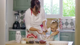 Happy little girl mixing the dough for a homemade berry pie under the watchful eye of her mother as they work together in the kitchen