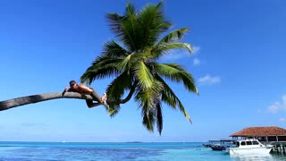 Happy Man Lying on Palm Tree Above Sea Water