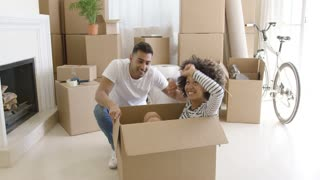 Happy mixed race couple having fun break with unpacking their boxes after moving in to a new apartment. Girl sitting on the floor inside the box and laugh.