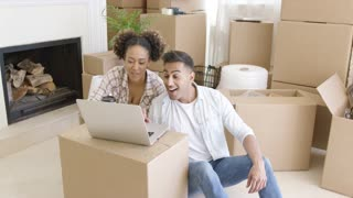 Happy mixed race couple sitting on the floor among unpacked carton boxes and using laptop computer to plan the future in their new apartment they just moved in.