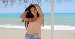 Happy Pretty Young Woman Under a Beach Umbrella