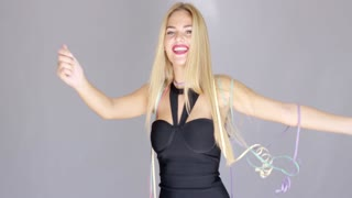 Happy sexy blond young girl having fun on a party. She thowing confetti in the air and smiling. Wearing elegant black evening dress. Dancing to the music while isolated on gray.