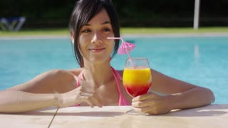 Happy smiling young woman with a fruity tropical cocktail relaxing in a resort swimming pool on summer vacation