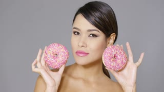 Happy vivacious gorgeous young woman holding two pink donuts in her hands head and shoulders over grey
