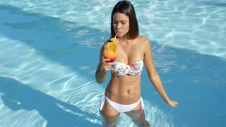 Happy vivacious woman with a tropical cocktail in her hand standing in the cool water of a swimming pool at a summer vacation resort