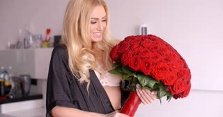 Happy Woman in Nightwear Holding Red Rose Bouquet