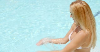 Happy Woman in the Swimming Pool Splashing Water