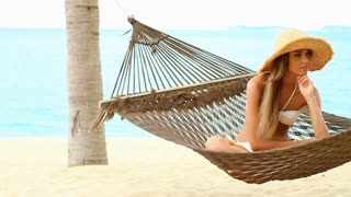Happy woman on hammock at the exotic beach