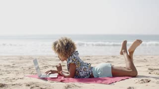 Happy Woman Typing On A Laptop On A Beach