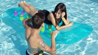 Happy young adult couple floating together on inflatable floating plastic mattress in outdoor pool