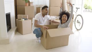 Happy young couple moving house together with the pretty young woman sitting inside a brown cardboard box with her husband crouching alongside smiling