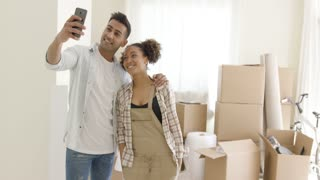 Happy young couple posing for a selfie in their new home in front of a pile of brown cardboard boxes