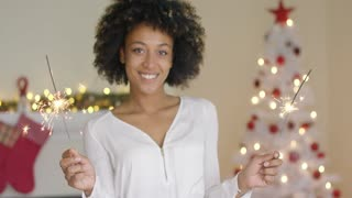 Happy young woman celebrating Christmas at home in front of the tree grinning as she holds two burning sparklers in her hands