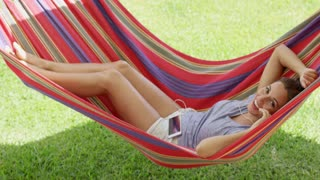 Happy young woman relaxing in a colorful hammock outdoors in the shade in the garden looking up at the camera with a smile as she listens to music on her mobile.