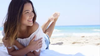 Happy young woman relaxing in the shade of an umbrella on the beach lying facing the camera with a lovely friendly smile