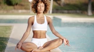 Healthy Woman Meditating Near The Pool