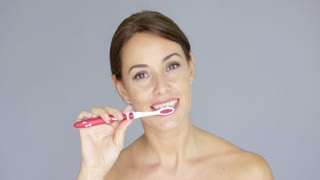 Healthy young woman cleaning her teeth with a toothbrush as she smiles at the camera head and shoulders on grey