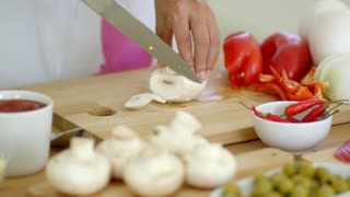 Housewife preparing dinner slicing fresh mushrooms on a wooden chopping board on a kitchen counter close up low angle on her hands