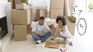 Hungry young couple eating a pizza on the floor of the living room while packing up their home to move house surrounded by brown boxes