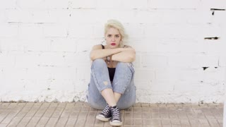 Introvert young woman sitting on brick paving leaning against a white exterior wall thinking and staring at the camera