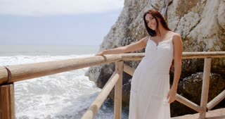 Lady Holding at Beach Railing with Air Blown Hair