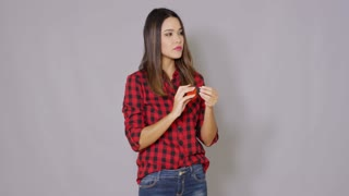 Laughing DIY woman in a colorful red plaid shirt holding up a tape measure in front of her face isolated on grey with copy space